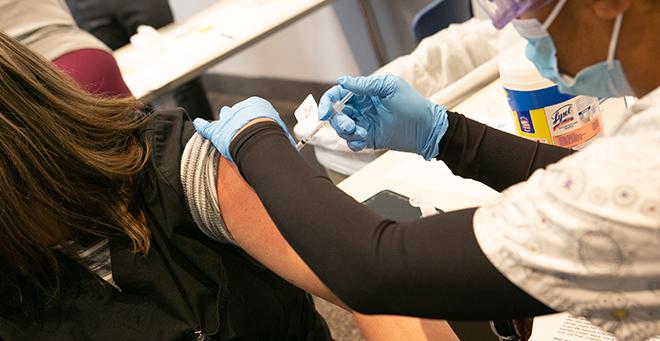 A UMass medical student vaccinating an individual