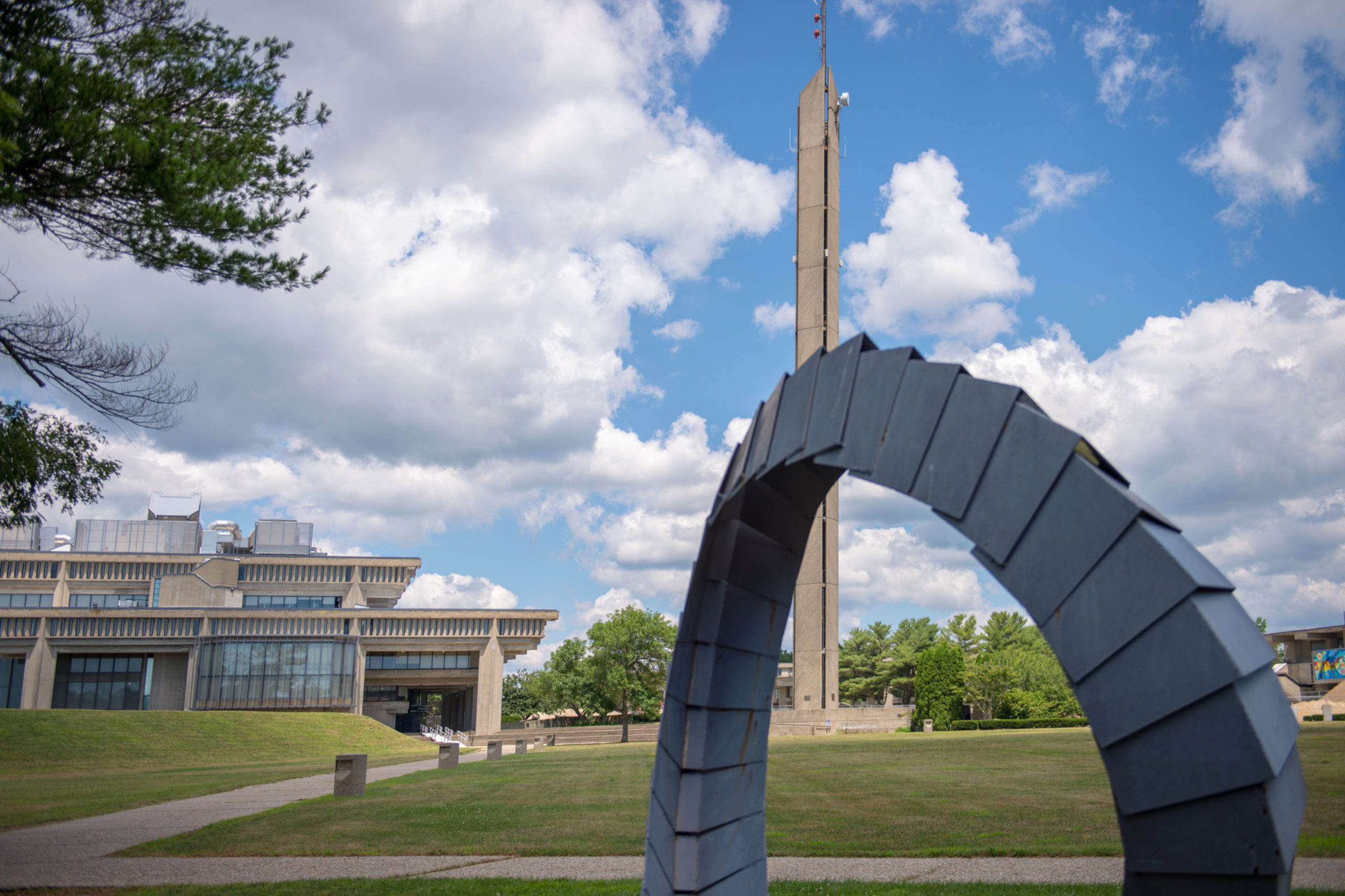 Campus arch sculpture pictured in front of UMass Dartmouth campanile