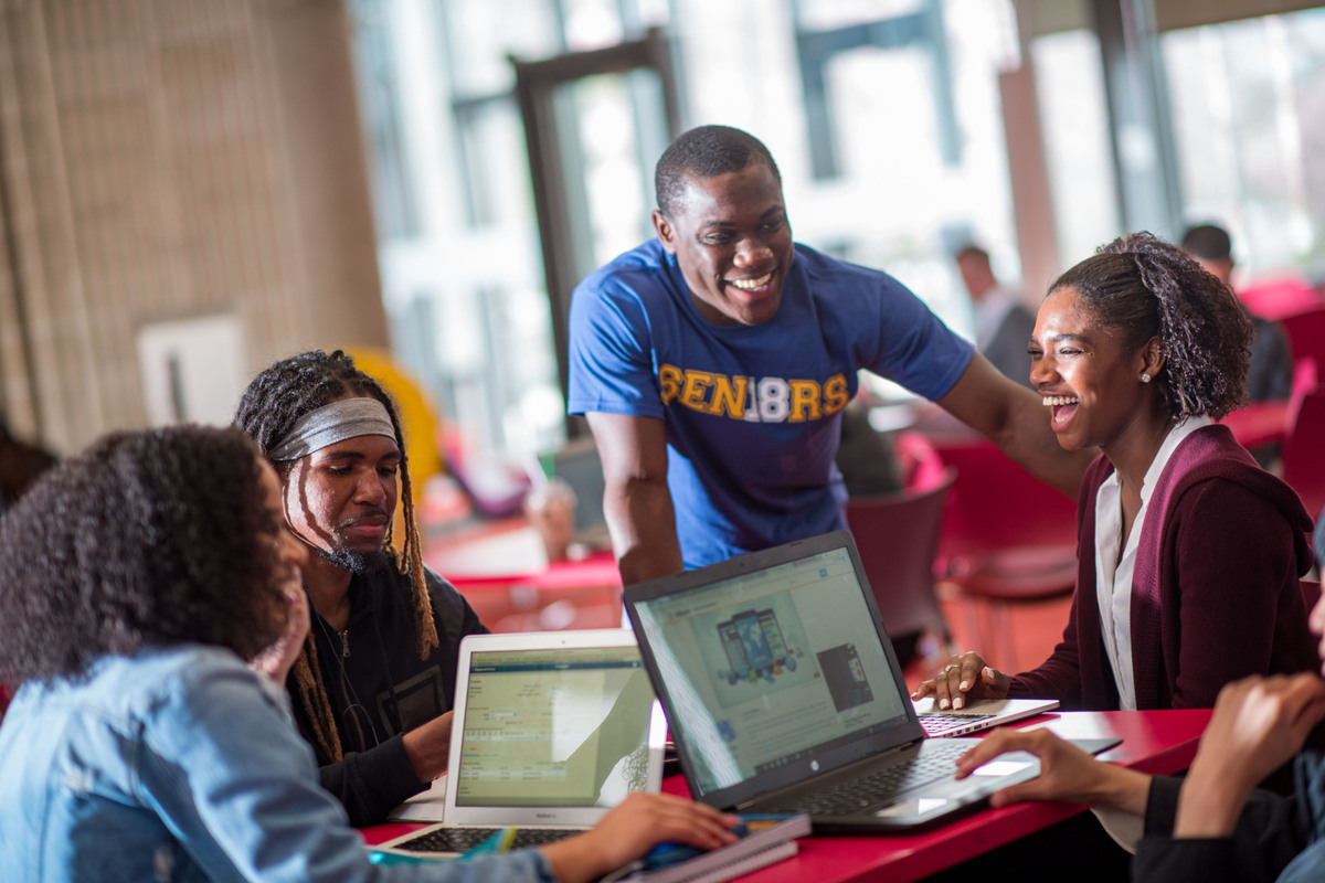 Four students work in a group together on UMass Dartmouth campus